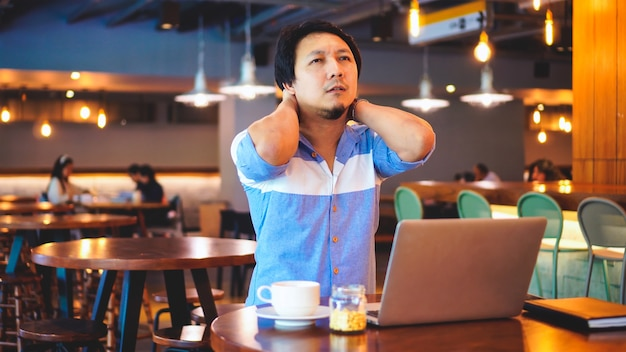 Asian businessman in casual suit working which have symptom is neck pain, backache, headac