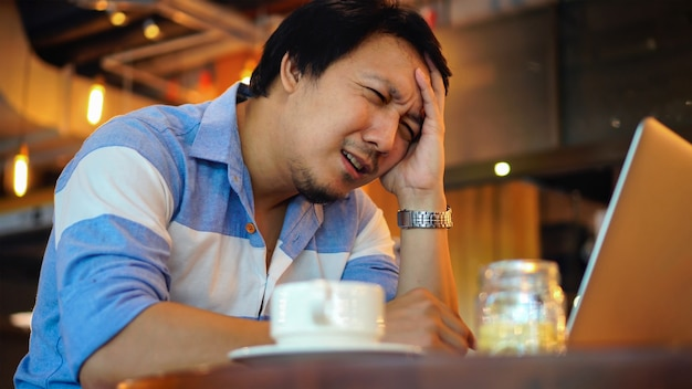 Asian businessman in casual suit working with computer in stress emotion at co-working spa