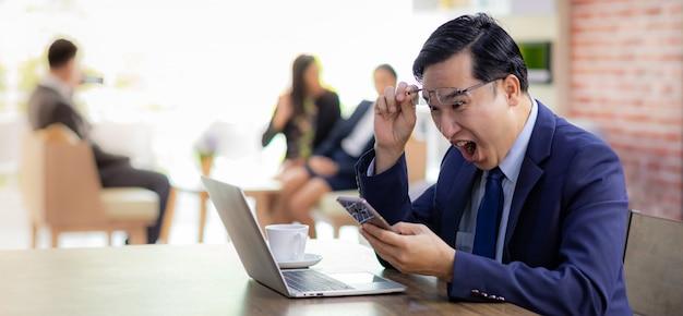 Asian businessman celebrate in cafe