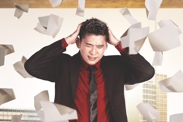 Asian businessman feeling depressed with flying work papers