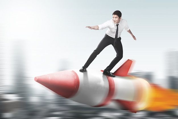Asian businessman flying on a rocket