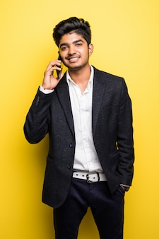 Asian businessman handsome man wi talk on smart phone on yellow wall