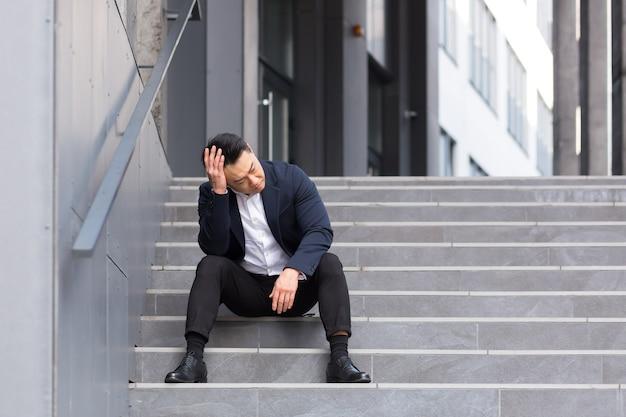 アジアのビジネスマンは、オフィスの近くの階段に座ってひどい頭痛を持っています