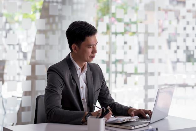 연필 들고 아시아 사업가 노트북에서 작동하고 사무실에서 메모를 걸립니다.