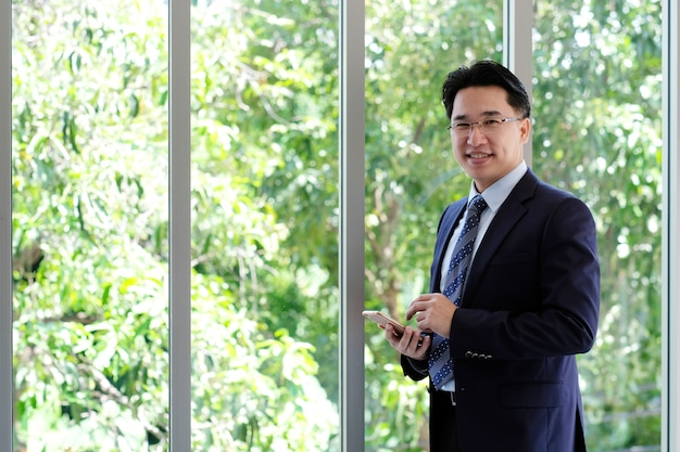 Asian businessman holding smart phone standing by windows, inside eco office building