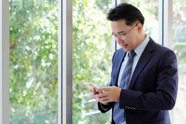 Asian businessman holding smart phone with happy smiling face standing by windows
