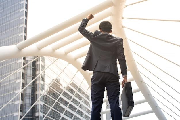 Азиатский бизнесмен, проведение портфель и оружия, стоя в центре города с работой, чтобы добиться успеха