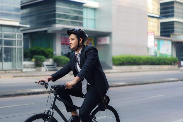スーツを着たアジア人ビジネスマンが、朝の通勤のために街の通りを自転車で走っています。エコ輸送コンセプト。