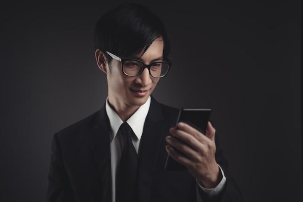 Азиатский бизнесмен в черном костюме счастливым и смотря умный телефон.