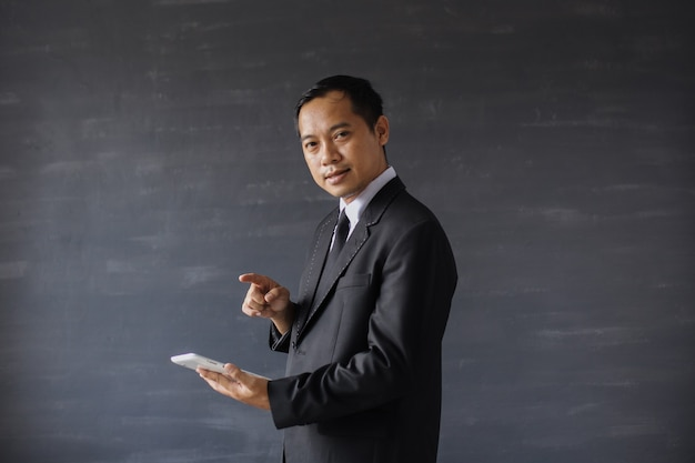스마트폰을 가리키며 카메라를 바라보는 검은 양복을 입은 아시아 사업가