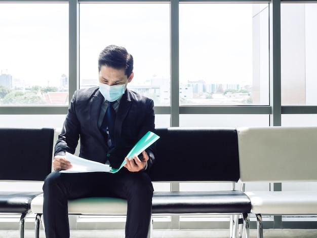 검은 양복에 아시아 사업가 앉아 보호 얼굴 마스크를 착용하고 그의 이력서를 검토하고 거대한 유리 창 근처에서 면접을 기다리고