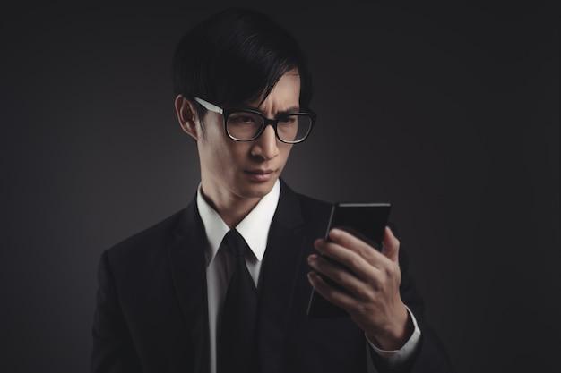 Азиатский бизнесмен в черном костюме беспокоится и смотрит на смартфон.