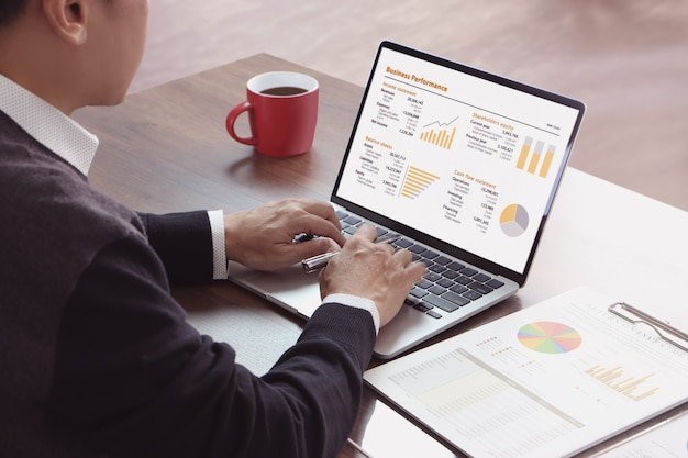 Азиатский бизнесмен в повседневной одежде с помощью портативного компьютера проверяет финансовые показатели возврата инвестиций, рентабельности инвестиций и эффективности бизнеса.