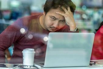 深刻な、疲れた行動で働くための技術ラップトップを使用してカジュアルスーツのアジアのビジネスマン