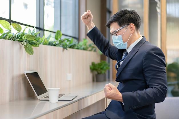 Азиатский бизнесмен в костюме и в защитной медицинской маске поднимает руку, чтобы отпраздновать успех в работе, глядя на ноутбук на рабочем месте