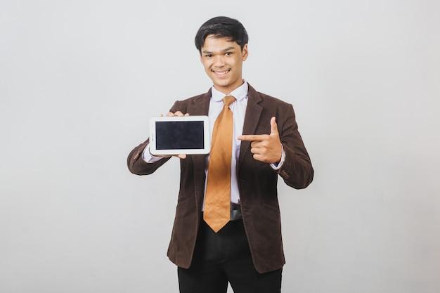 양복 재킷과 넥타이 스마트 폰의 빈 화면을 가리키는 아시아 사업가