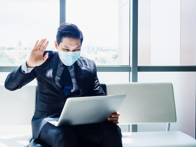 Азиатский бизнесмен в костюме в защитной маске махнул, чтобы поприветствовать коллег у монитора портативного компьютера на коленях