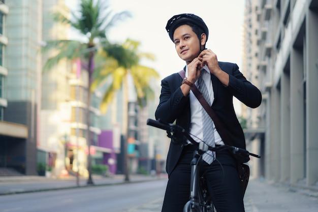 スーツを着たアジアのビジネスマンは、朝の通勤のために街を自転車で走る安全ヘルメットをかぶっています。エコ輸送。