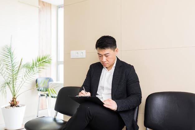 Азиатский бизнесмен в зале ожидания, сидя на стуле возле рецепции офисного центра
