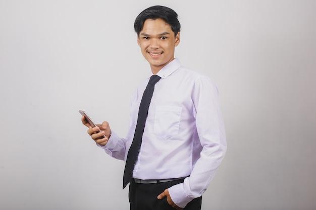 스마트 폰을 사용하고 카메라를 찾고 흰색 셔츠와 검은 넥타이에 아시아 사업가