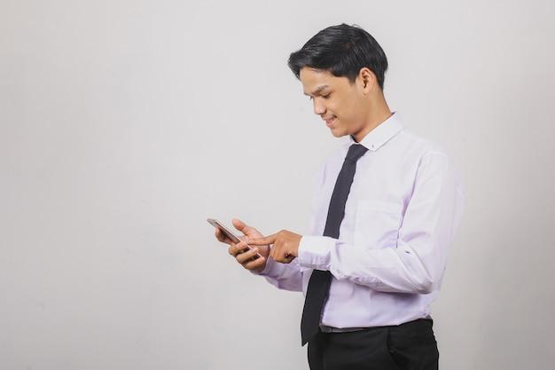 스마트 폰을 사용하여 흰색 셔츠와 검은 넥타이에 아시아 사업가