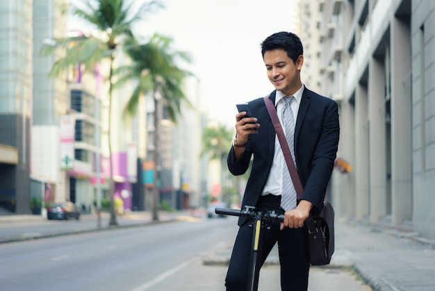 Asian businessman is riding an electric scooter and using his mobile phone to open a map in application to check the city road routes to work in the morning.