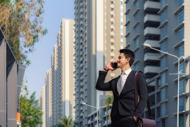 アジアのビジネスマンが立って、彼の同僚と話している