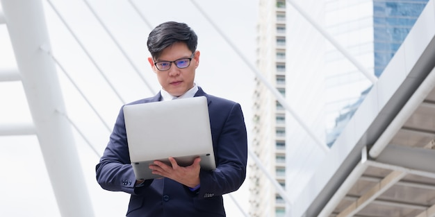 Asian businessman is working on a laptop while standing outdoors.