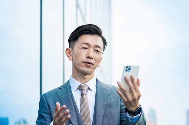 Азиатский бизнесмен, глядя на экран смартфона