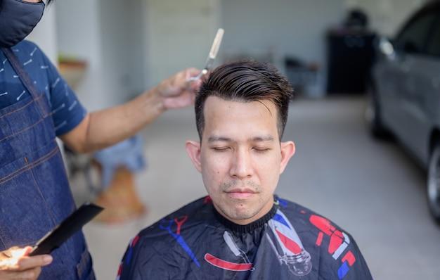 自宅で散髪やサロンを作るアジアのビジネスマン。庭の屋外理髪店。社会的距離と新しい通常のライフスタイル。
