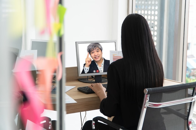 Asian businessman making a video call to customer for talking and presenting work through the video conference.