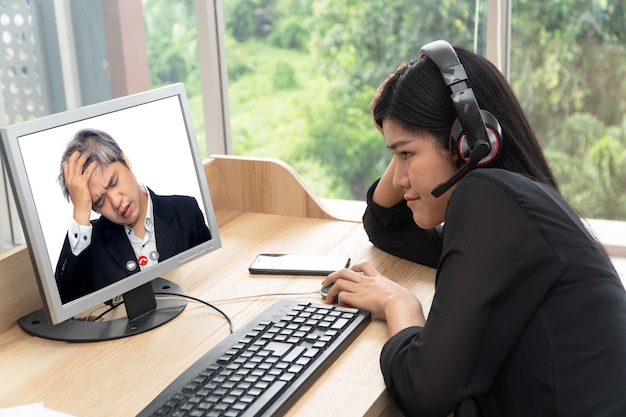 Asian businessman making a video call the subordinate for talking about problems of work through the video conference.