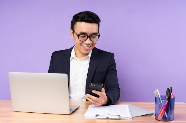 紫色の背景で隔離、机の上に座っているアジアの実業家男性