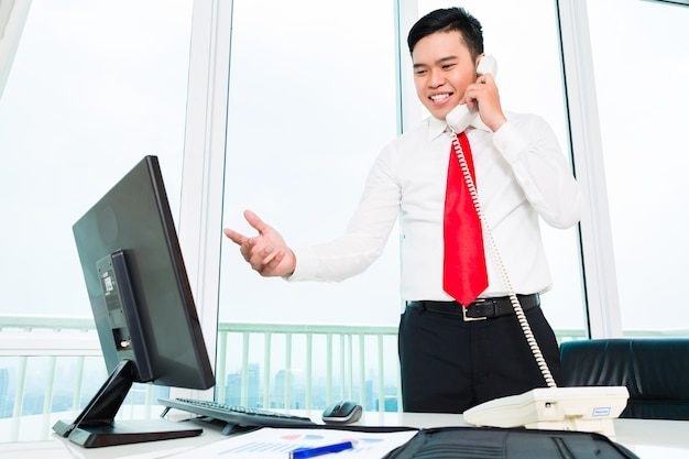 Asian businessman  on phone working in office