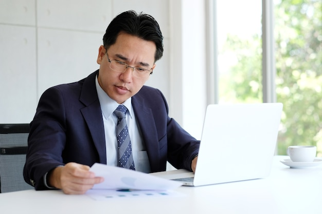 Asian businessman reading papers and working with laptop computer at office