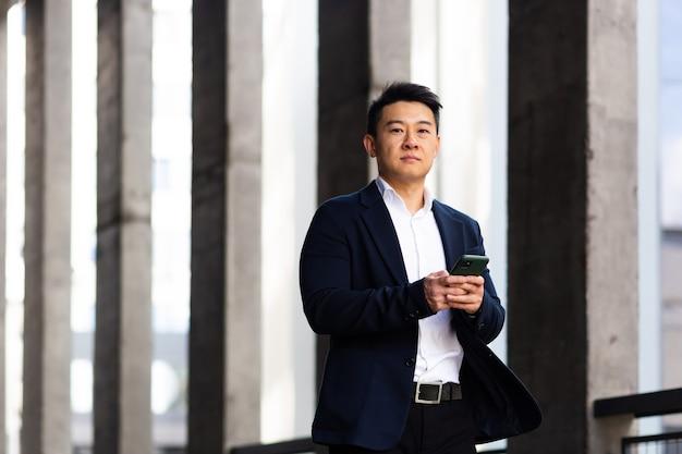 アジアのビジネスマンは、外のオフィスの近くのカメラを真剣に見て電話からニュースを読みます