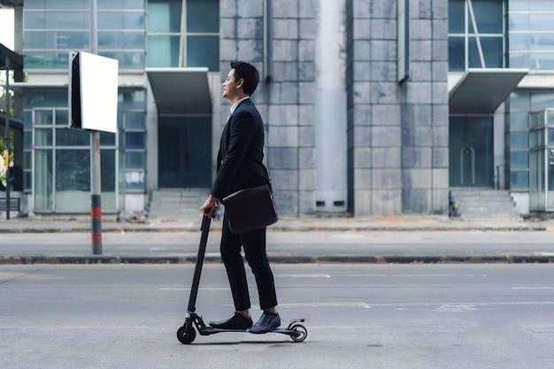 朝、仕事に行くために街の通りで電動スクーターに乗っているアジアのビジネスマン。今日の仕事の世界を最もよく反映する毎日の通勤。