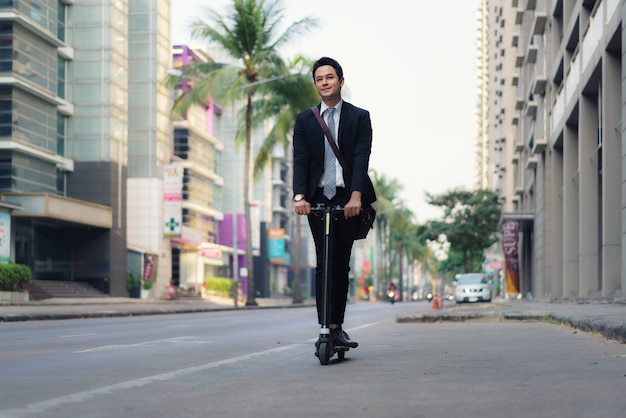 Asian businessman riding an electric scooter on the city streets to go to work in the morning.