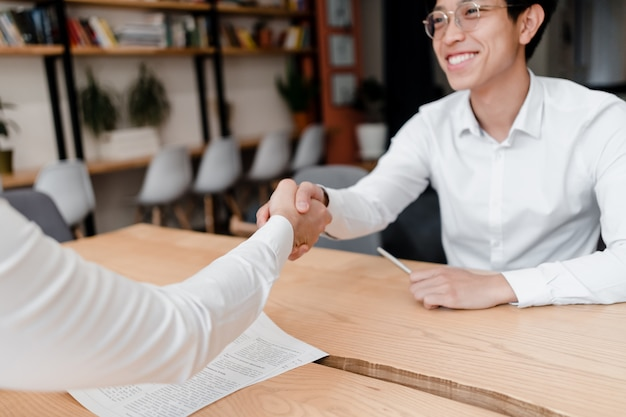 Asian businessman shakes hand on a deal