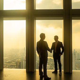 オフィスで握手するアジアのビジネスマン。