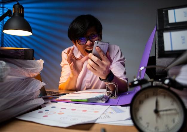 아시아 사업가는 밤에 근무 마감 시간에 동의할 수 없고 스트레스를 받은 후 휴대전화로 소리를 지릅니다.