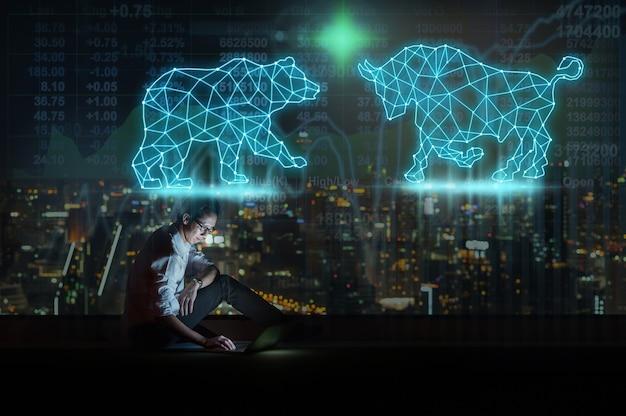 황소와 곰을 보여주는 스마트 휴대폰을 사용하여 앉아 있는 아시아 사업가