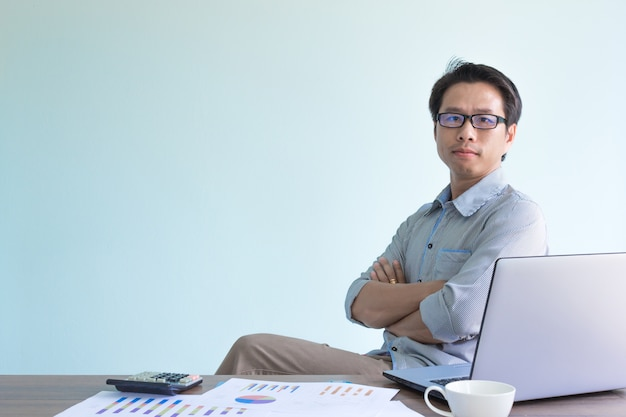 Asian businessman sitting in office and crossing his arms