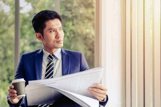 Asian businessman sitting reading newspaper in office smile on face