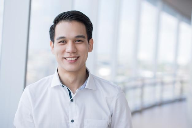 明るくモダンなオフィスで一人で立っている間自信を持って笑っているアジアのビジネスマン
