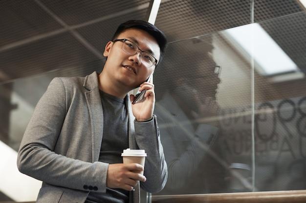 Азиатский бизнесмен, выступая на смартфон в офисе