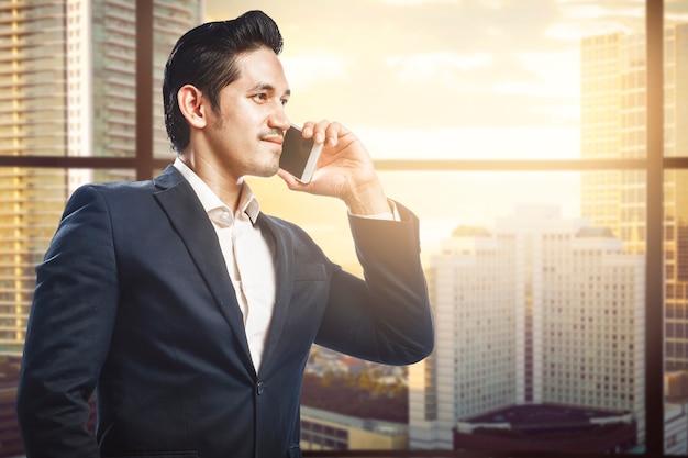 아시아 사업가 서 사무실 건물에 휴대 전화로 이야기