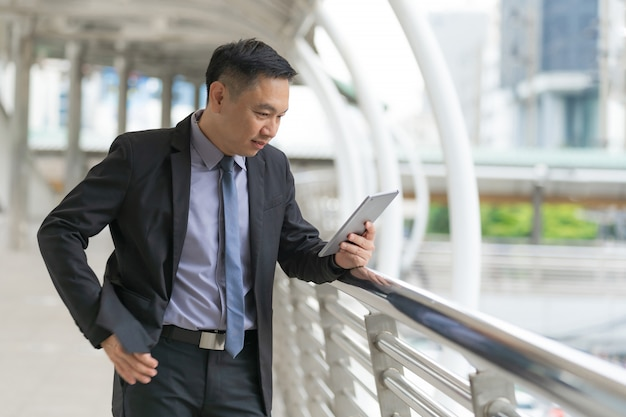 Asian businessman standing and holding digital tablet with business office buildings