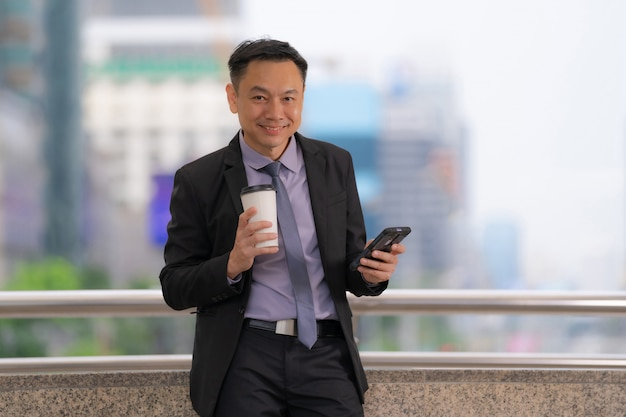 Asian businessman standing and holding mobile phone with business office buildings in the city