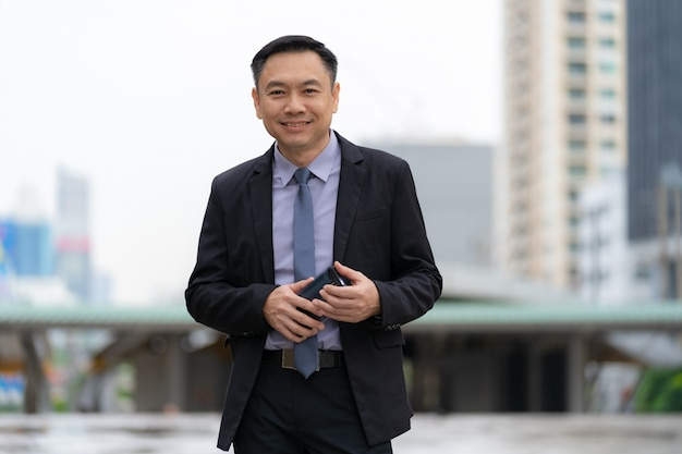 Asian businessman standing and holding mobile phone